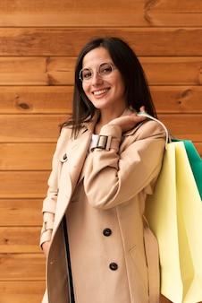 Mujer sonriente con gafas posando sosteniendo bolsas de la compra.