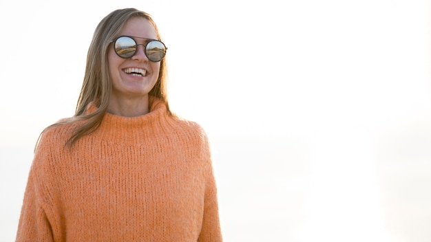 Mujer sonriente con gafas de sol y cielo brillante