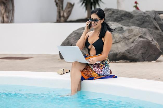 Mujer sonriente con gafas de sol hablando por teléfono en bikini sentada en el borde de la piscina con el portátil disfrutando de sus vacaciones de verano