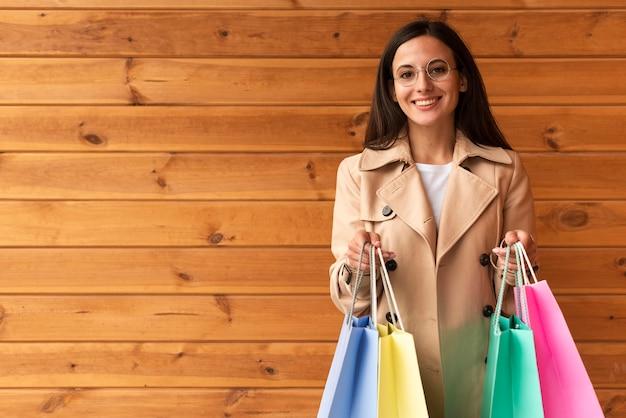 Mujer sonriente con gafas sosteniendo un montón de bolsas de la compra.