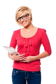 Mujer sonriente con gafas sosteniendo tableta digital