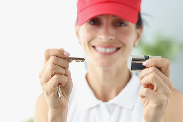 Mujer sonriente en gorra roja sosteniendo la llave y el ojo de la cerradura closeup