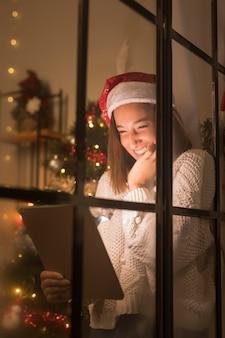 Mujer sonriente con gorro de papá noel a través de la ventana mirando tableta en navidad
