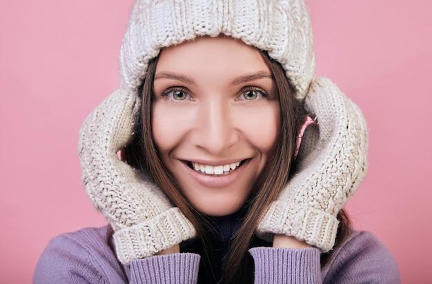 Mujer sonriente en un gorro de punto de invierno con las manos en guantes cerca de la cabeza