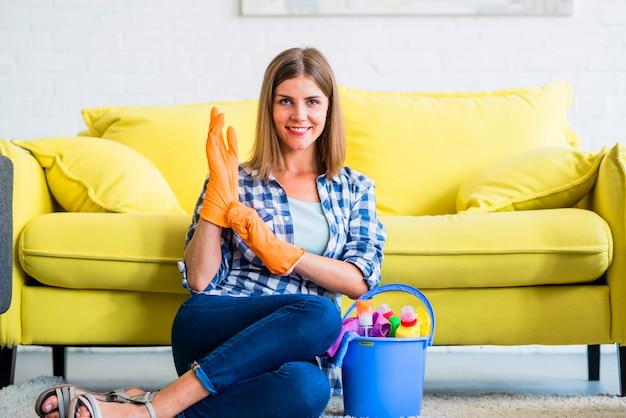 Mujer sonriente en guantes anaranjados que se sientan con equipos de limpieza en el cubo