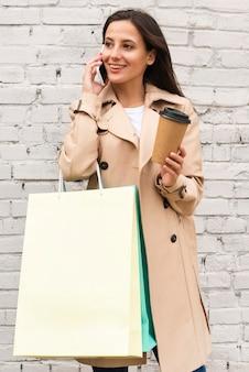 Mujer sonriente hablando por teléfono al aire libre mientras sostiene la taza de café y bolsas de compras