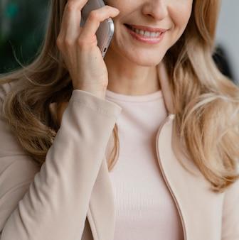 Mujer sonriente hablando por teléfono de cerca
