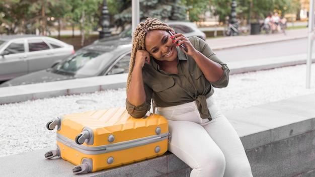 Mujer sonriente hablando por teléfono junto a su equipaje de viaje