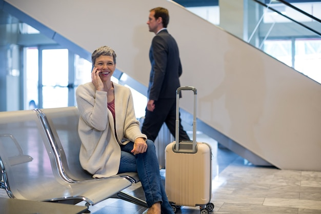 Mujer sonriente hablando por teléfono móvil en la sala de espera