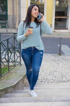 Mujer sonriente hablando por teléfono y subiendo las escaleras de la ciudad