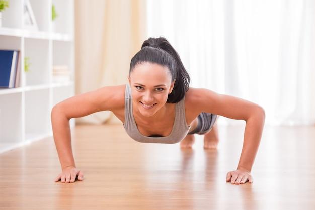 La mujer sonriente está haciendo ejercicios en casa.