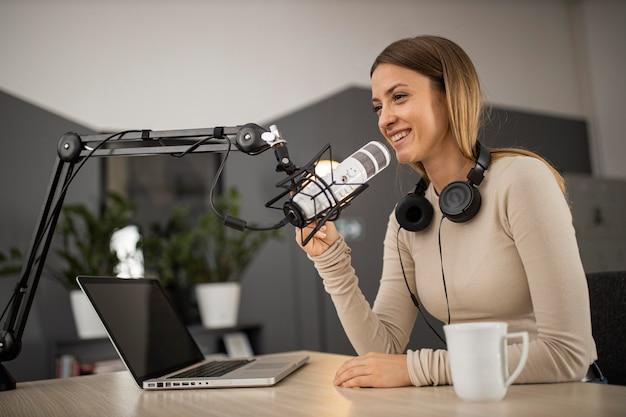 Mujer sonriente haciendo un podcast en la radio con un micrófono y una computadora portátil