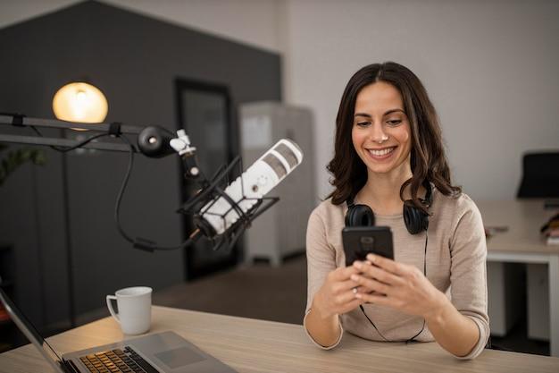 Mujer sonriente haciendo un podcast en la radio con un micrófono y un teléfono inteligente