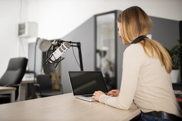Mujer sonriente haciendo radio con laptop y micrófono