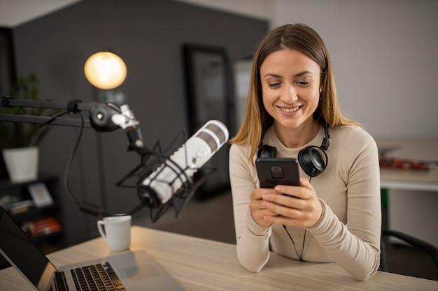Mujer sonriente haciendo radio con micrófono y smartphone