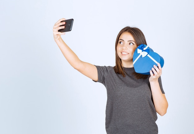 Una mujer sonriente haciendo selfie con una caja de regalo en forma de corazón.