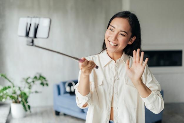 Mujer sonriente haciendo un vlog en casa