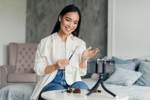 Mujer sonriente haciendo un vlog sobre maquillaje en interiores