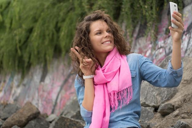 Mujer sonriente hermosa feliz joven que hace a uno mismo en el teléfono de la cámara