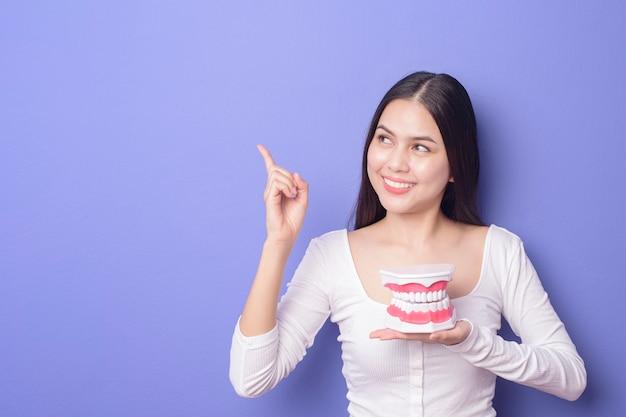 La mujer sonriente hermosa joven está sosteniendo los dientes plásticos de la dentadura sobre púrpura aislada