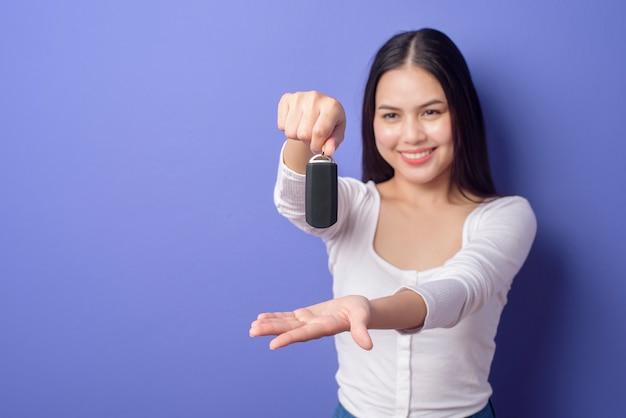 La mujer sonriente hermosa joven está sosteniendo la llave del coche sobre púrpura aislada