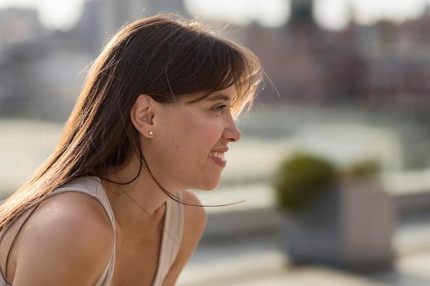 Mujer sonriente hermosa de lado que presenta