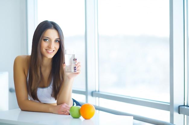 Mujer sonriente hermosa que toma la píldora de la vitamina. suplemento dietético