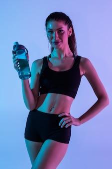 Mujer sonriente con hermoso cuerpo beber agua después del entrenamiento, aislado en luz púrpura con copyspace para texto