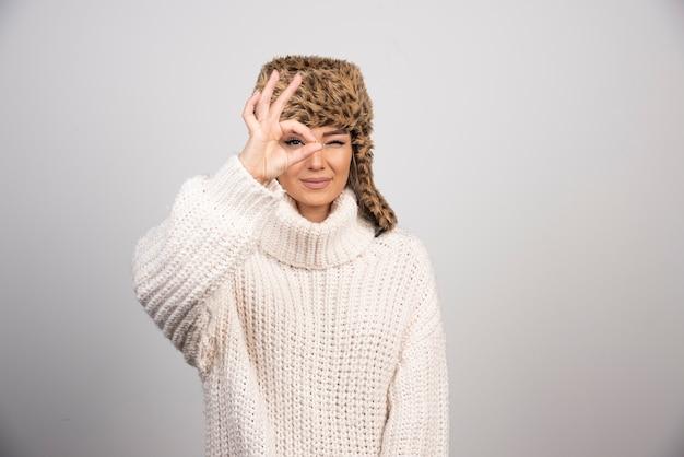Una mujer sonriente en un hermoso sombrero haciendo bien los ojos gesto mirando a través de los dedos.