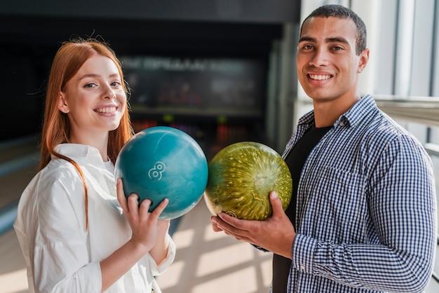 Mujer sonriente y hombre con bolas de colores en un club de bolos