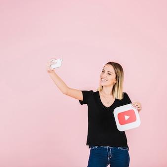 Mujer sonriente con icono de youtube tomando selfie desde teléfono móvil