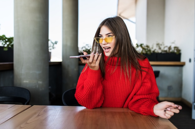 Mujer sonriente joven belleza sentada en un café y hablando por el teléfono celular