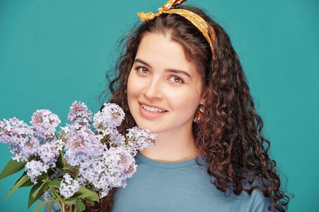 Mujer sonriente joven en camiseta con diadema sosteniendo un ramo de lilas y disfrutando de su olor mientras te mira contra la pared azul
