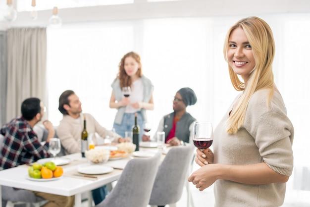 Mujer sonriente joven con copa de vino tinto, amigos interculturales habiendo hablado por mesa servida