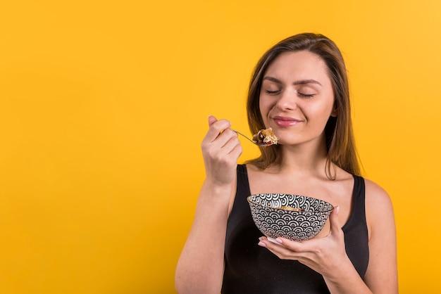 Mujer sonriente joven con la cuchara y el tazón de fuente de escamas