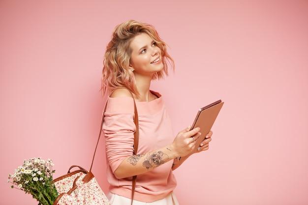 Mujer sonriente joven del estudiante del inconformista con el peinado y el tatuaje rosados coloreados rizados