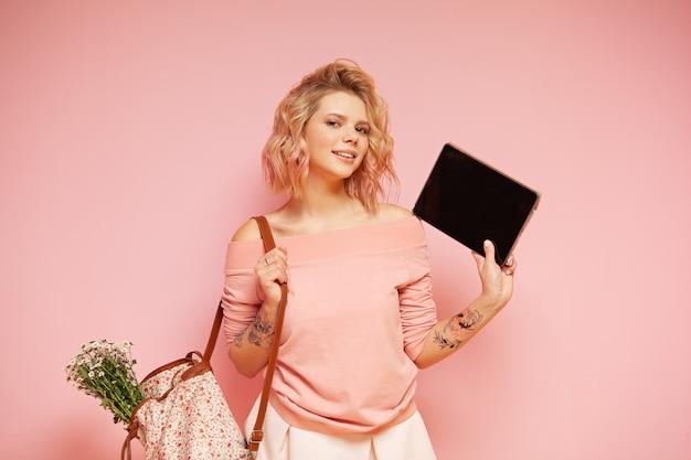 Mujer sonriente joven del estudiante del inconformista con la tableta rosada coloreada rizada del peinado y de la tenencia del tatuaje