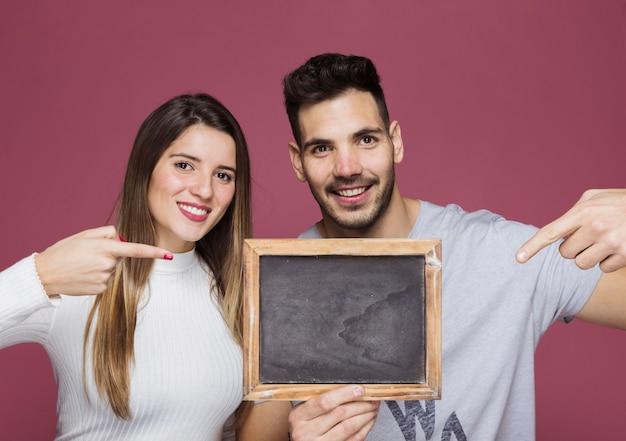 Mujer sonriente joven y hombre positivo que señalan en el marco de la foto