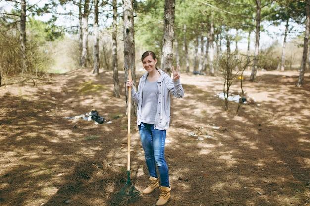 Mujer sonriente joven limpiando con rastrillo para la recolección de basura y mostrando el signo de la victoria en el parque lleno de basura