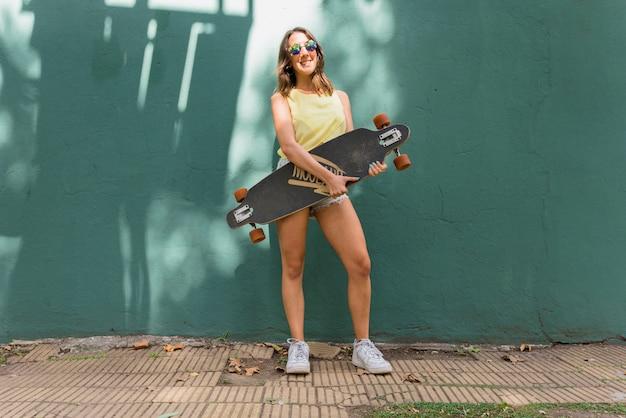 Mujer sonriente joven con longboard contra la pared verde
