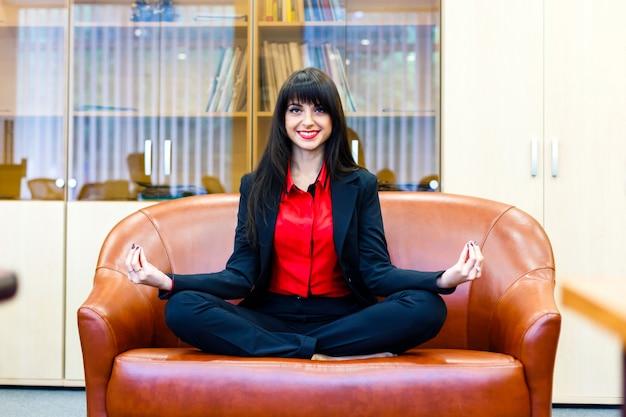 La mujer sonriente joven medita en el sofá en oficina