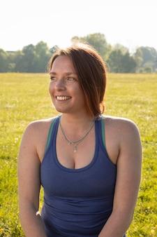 Mujer sonriente joven meditando al aire libre