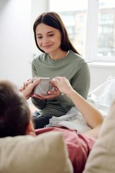 Mujer sonriente joven mirando a su marido enfermo acostado en el sofá mientras le da una bebida caliente, tocando su mano y sonriendo contra la ventana