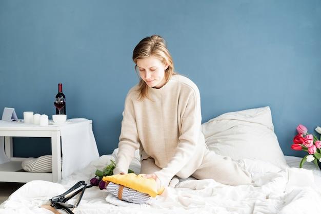 Mujer sonriente joven organizando ropa sentada en la cama en casa