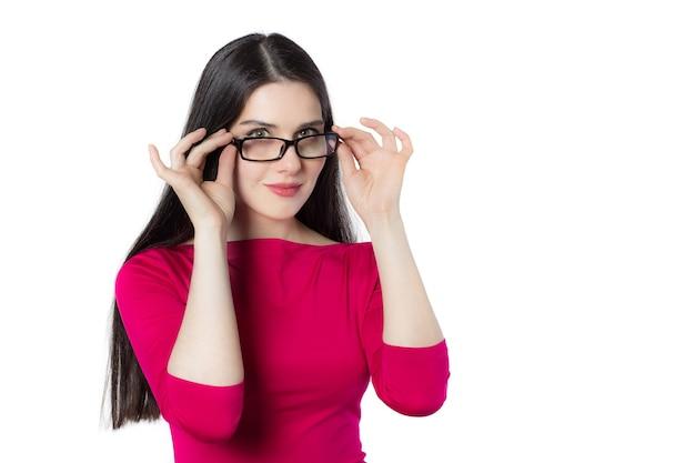 Mujer sonriente joven profesional inteligente del estudiante en la camisa roja que toca los vidrios que piensan nueva idea en el fondo blanco, idea del concepto de la mujer del conocimiento