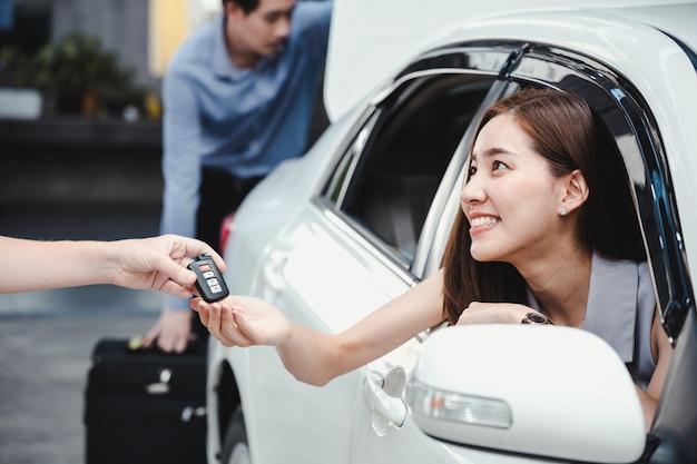 Mujer sonriente joven que consigue la llave de un coche nuevo.