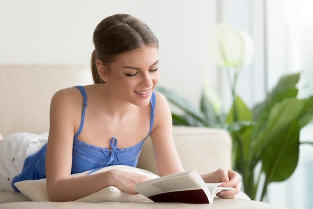 Mujer sonriente joven que lee el libro interesante en el sofá en casa