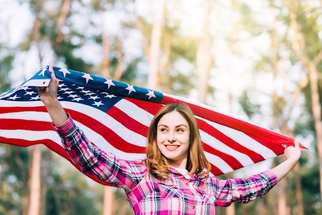 Mujer sonriente joven que lleva la bandera de los eeuu el día de la independencia