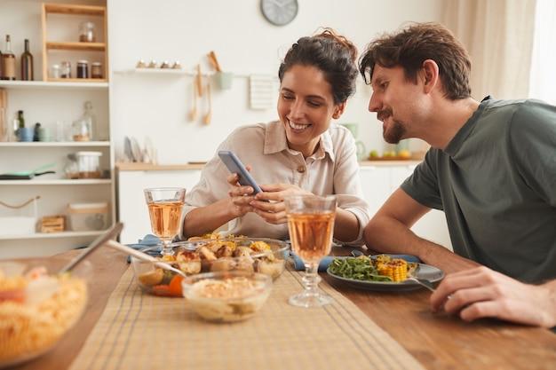 Mujer sonriente joven que muestra algunas fotos en su teléfono móvil a su novio durante la cena en la cocina de casa