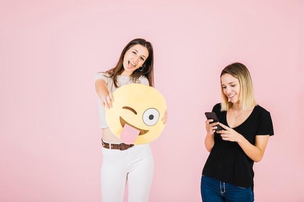 Mujer sonriente joven que sostiene el emoji del ojo de guiño cerca de su amigo que usa el teléfono móvil